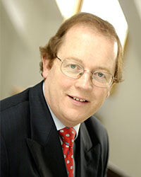 man in a suit with glasses looking in to the camera