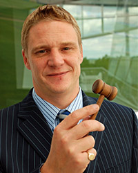 man in a suit with a small wooden hammer